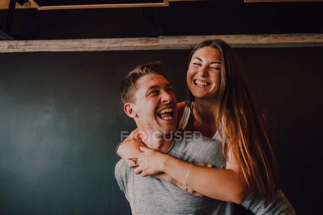 Aufgeregte erwachsene Mann in Sportbekleidung huckepack schlanke junge Frau, während sie vor schwarzer Wand in der modernen Turnhalle stehen — Stockfoto