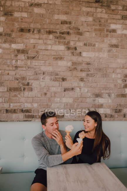 Hohe Winkel von fröhlichen Mann und junge Frau in lässiger Kleidung suchen und füttern einander mit leckerem Eis, während sie am Tisch auf dem Sofa sitzen und entspannen zusammen in modernen Café im Loft-Stil — Stockfoto
