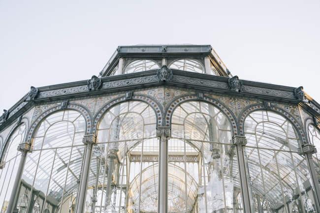 Castillo geométrico antiguo con ventanas de cristal que reflejan árboles, Palacio de Cristal, Parque del Retiro, Madrid, España. - foto de stock