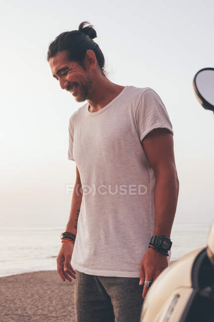Happy adult ethnic male in casual t shirt standing next to motorbike at beach at sunset time. - foto de stock