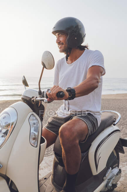 Side view of happy active guy dressed in white t shirt with shorts and black helmet riding scooter in summer evening on beach — Stock Photo