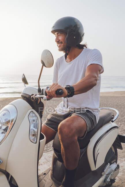 Seitenansicht von glücklichen aktiven Kerl in weißem T-Shirt mit kurzen Hosen und schwarzem Helm Roller fahren im Sommer Abend am Strand gekleidet — Stockfoto