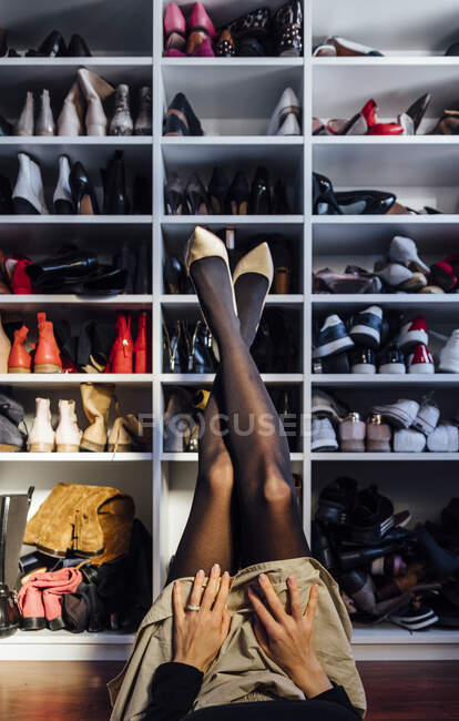 Crop female crossed legs in black tights and white high heel shoes with modern closet on background — Stock Photo