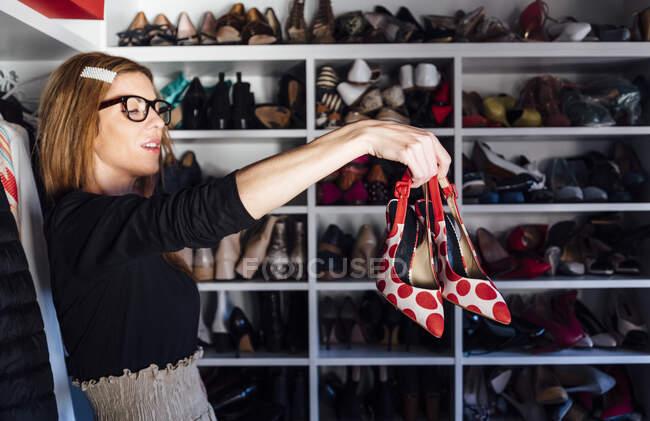 Seitenansicht der stilvollen Frau in Brille, die in ausgestrecktem Arm rot-weiße High Heels mit modernem Kleiderschrank auf dem Hintergrund hält — Stockfoto