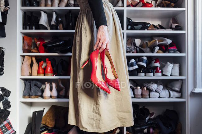 Side view of cropped unrecognizable stylish woman in skirt holding fashionable red high heels shoes with modern closet on background — Stock Photo