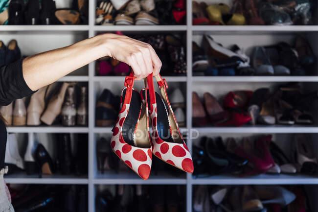 Cortado mão mulher irreconhecível segurando sapatos de salto alto vermelho e branco com armário moderno no fundo — Fotografia de Stock
