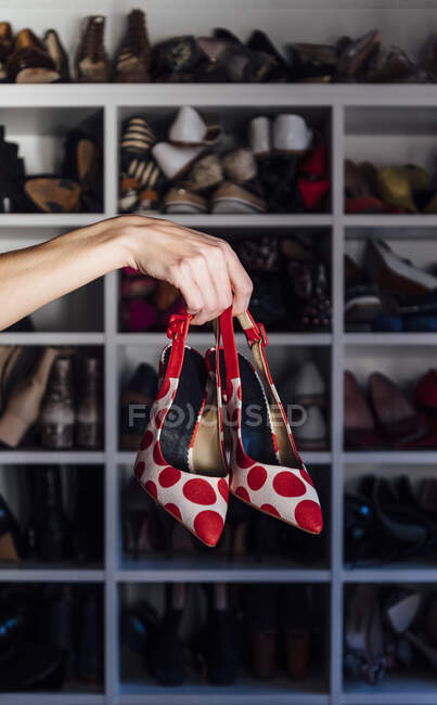 Cropped unrecognizable woman hand holding red and white high heels shoes with modern closet on background — Stock Photo