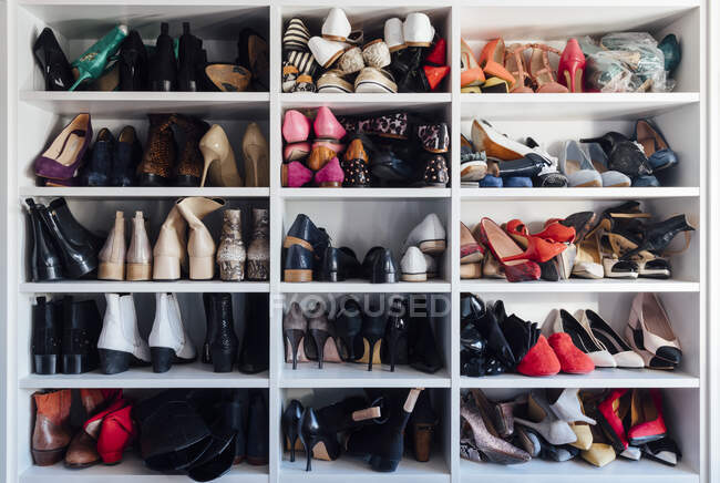 Modern white closet and square shelves with female colorful expensive high heels shoes and sneakers — Stock Photo