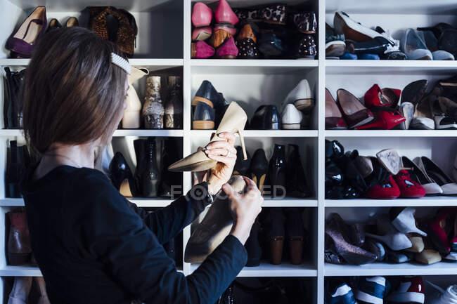 Vista lateral da mulher elegante em óculos segurando sapatos de salto alto na moda com armário moderno no fundo — Fotografia de Stock