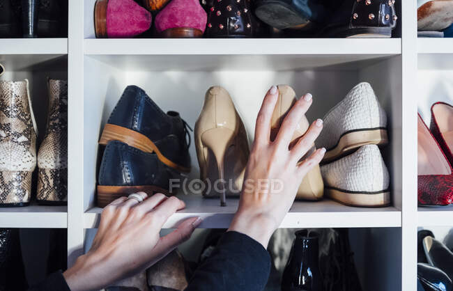 Cropped unrecognizable woman hands taking beige high heels shoes from shelf of modern white closet — Stock Photo