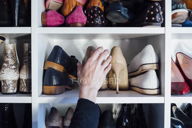 Cortado mãos mulher irreconhecível tendo bege sapatos de salto alto da prateleira do armário branco moderno — Fotografia de Stock