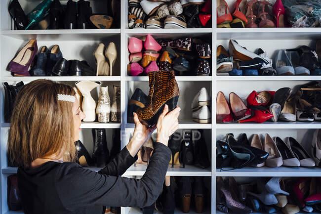 Vista lateral da mulher tomando sapatos de salto alto bege da prateleira do armário branco moderno — Fotografia de Stock