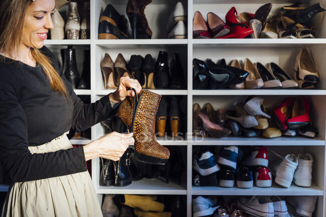 Side view of stylish woman in glasses holding fashionable high heels boots shoes with modern closet on background — Stock Photo
