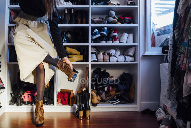 Cortar mulher anônima em roupa elegante tentando em botas de salto alto sapatos coloridos no guarda-roupa moderno — Fotografia de Stock