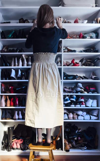 Visão traseira da mulher sem rosto em pé em um banquinho de madeira tomando bege sapatos de salto alto da prateleira do armário branco moderno — Fotografia de Stock
