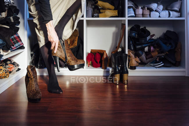 Crop anonymous woman in stylish outfit trying on high heels boots colorful shoes in modern wardrobe — Stock Photo