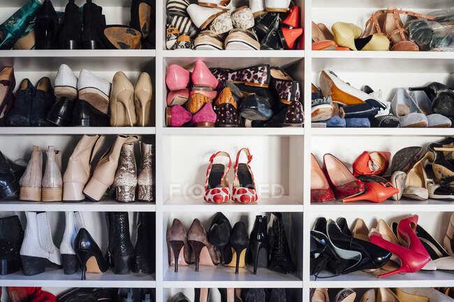 Armadio bianco moderno e scaffali quadrati con scarpe e scarpe da ginnastica con tacchi alti colorati femminili — Foto stock