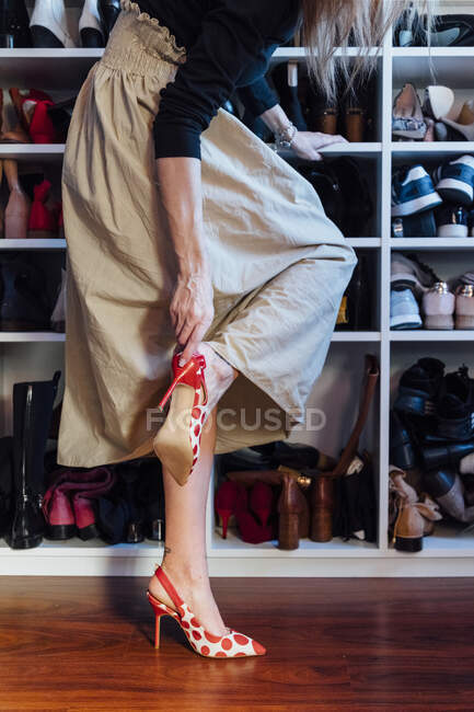 Crop anonymous woman in stylish outfit trying on high heels colorful shoes in modern wardrobe — Stock Photo