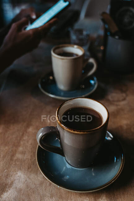 Crop hands of unrecognizable female sitting on the background holding mobile phone on wooden table near hot coffee in a rustic mug — Stock Photo