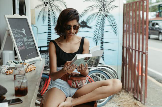 Mulher descansando no desgaste casual e óculos de sol na moda ler livro durante o refresco no bar ao ar livre — Fotografia de Stock