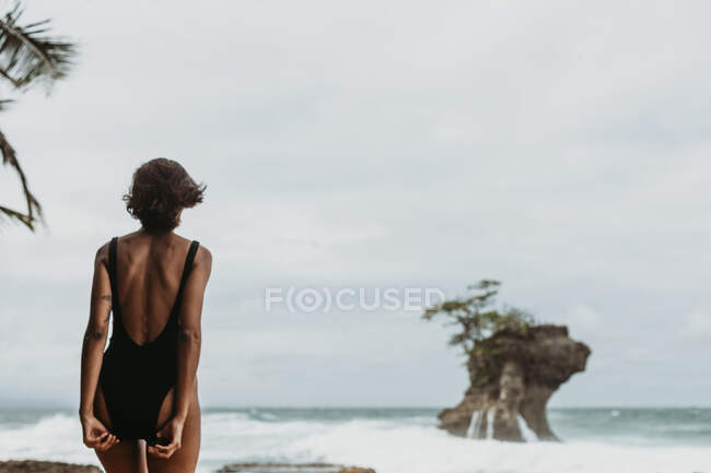 Back view of woman in black swimsuit walking on empty sandy coast with stormy ocean in overcast on background — Stock Photo