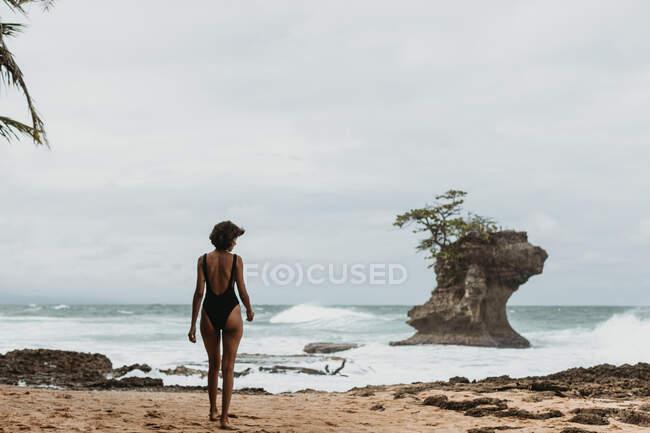 Rückansicht einer Frau im schwarzen Badeanzug, die an der leeren Sandküste mit stürmischem Ozean im bewölkten Hintergrund spaziert — Stockfoto