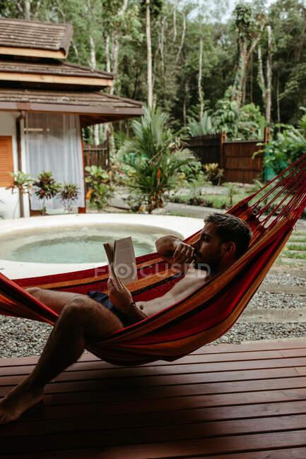 Vista lateral del viajero masculino en traje de baño escalofriante en la hamaca y libro de lectura en la piscina del hotel resort - foto de stock