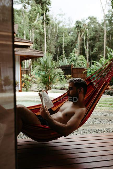 Vista lateral do viajante masculino em maiô refrigeração na rede e livro de leitura na beira da piscina do hotel resort — Fotografia de Stock