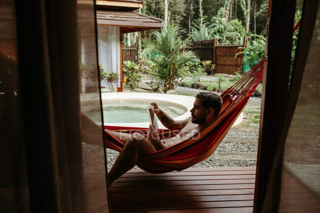 Side view of male traveler in swimsuit chilling on hammock and reading book at poolside of resort hotel — Stock Photo