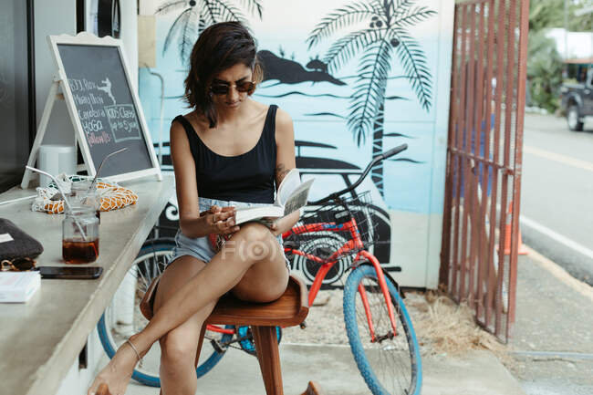 Resting woman in casual wear and trendy sunglasses reading book during refreshment in outdoors bar — Stock Photo