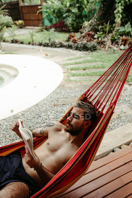 From above side view of male traveler in swimsuit chilling on hammock and reading book at poolside of resort hotel — Stock Photo