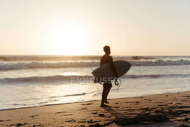 Back view of man silhouette holding surfboard while walking along sandy seashore in summertime during sunset — Stock Photo