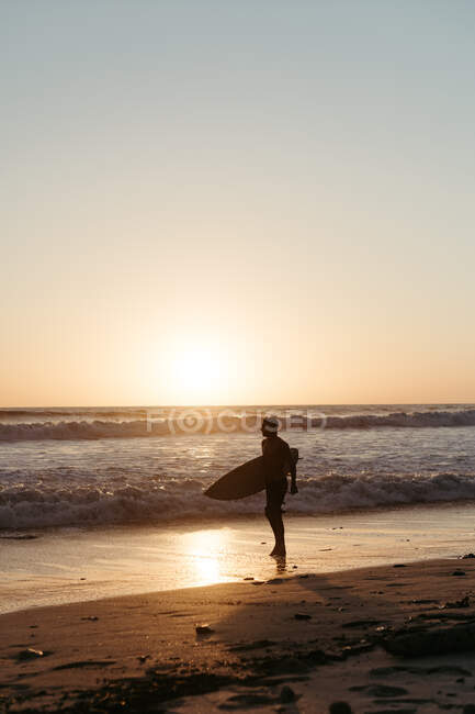 Side view of man silhouette holding surfboard while walking along sandy seashore in summertime during sunset — Stock Photo