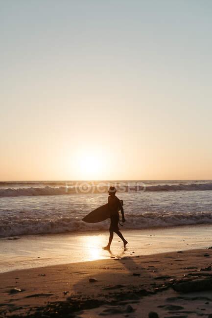 Вигляд людини на силует, що тримає серфінг під час прогулянки піщаним узбережжям влітку під час заходу сонця. — стокове фото