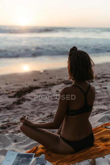Вид сзади на безликую женщину, практикующую йогу в позе лотоса и медитирующую на песчаном берегу в сумерках в летнее время — стоковое фото