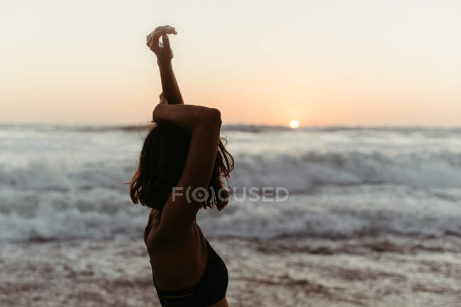 Вид сбоку на неузнаваемую женщину в бикини, поднимающую руки и созерцающую морской пейзаж на закате летом — стоковое фото
