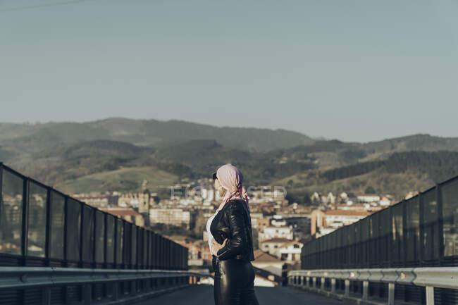 Mujer inspirada caminando por la carretera y mirando hacia el cielo - foto de stock