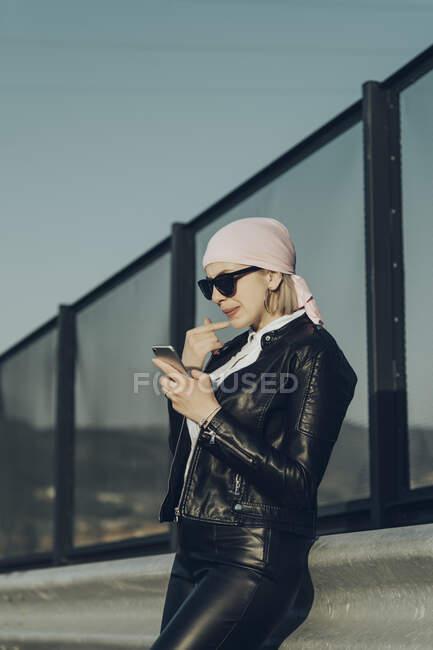 Стильная женщина, опирающаяся на дорожный забор и просматривающая смартфон — стоковое фото