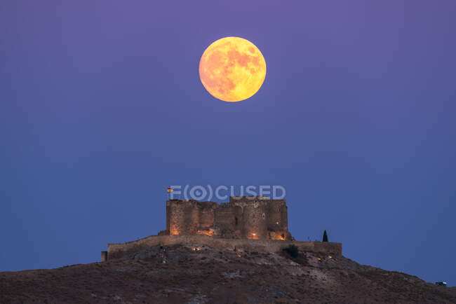From below picturesque scenery of abandoned aged fortress on top of mountain illuminated by full Moon at night in Toledo — Stock Photo