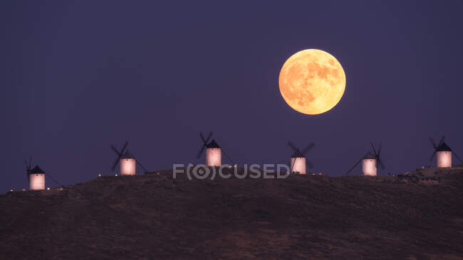 Amazing scenery of majestic full Moon over valley with windmills in sundown — Stock Photo