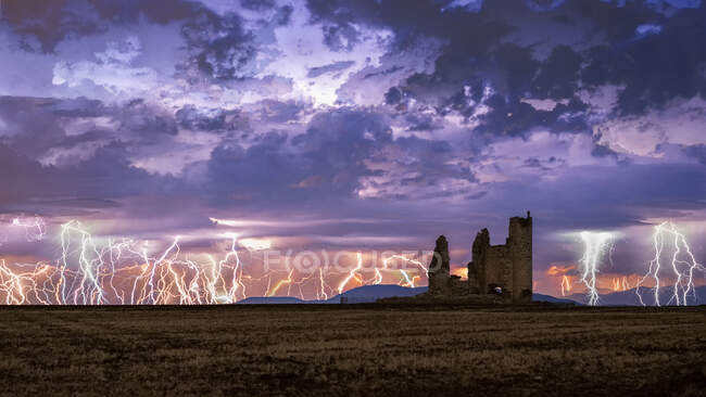 Amazing scenery of lightning storm on colorful cloudy sky over ruined old castle at night — Stock Photo