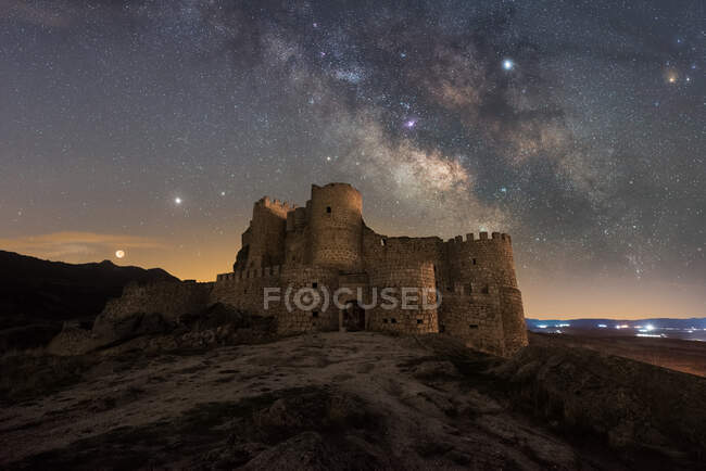 Удивительный пейзаж заброшенного древнего дворца на горе под красочным звездным небом ночью — стоковое фото