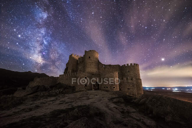 Amazing scenery of abandoned ancient palace on mountain under colorful starry sky at night — Stock Photo