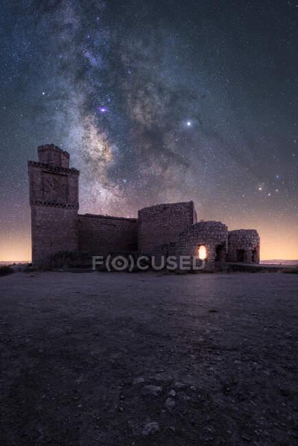 Increíble paisaje de palacio antiguo abandonado en la montaña bajo el colorido cielo estrellado en la noche - foto de stock
