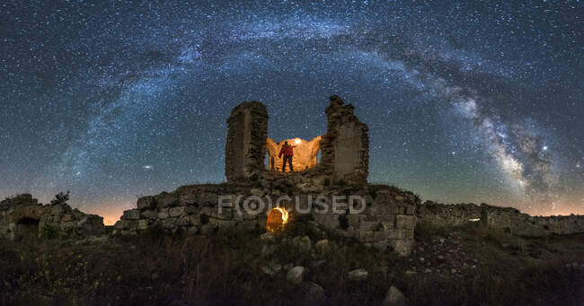 From below back view of anonymous tourist with lantern exploring ruined old castle under Milky Way at starry night — Stock Photo