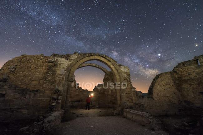 Vista trasera de los restos de turismo de viajeros sin rostro del antiguo castillo bajo la Vía Láctea en la noche estrellada - foto de stock