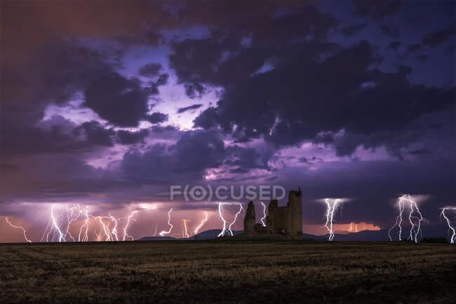 Удивительный пейзаж грозы на ярком облачном небе над разрушенным старым замком ночью — стоковое фото