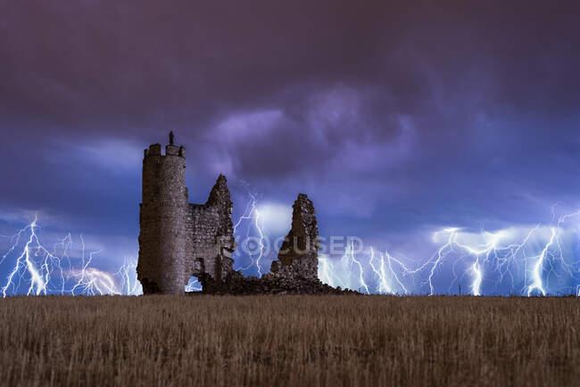 Вночі над зруйнованим старим замком нависає дивовижна блискавка. — стокове фото