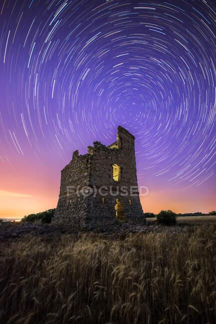 Живописный пейзаж древнего заброшенного замка под красочным звездным небом ночью — стоковое фото