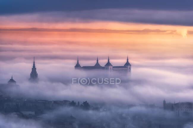 Сверху удивительный пейзаж средневекового замка, построенного над городом в туманном красочном восходе солнца — стоковое фото
